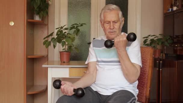 Älterer kaukasischer Mann macht Gewichthanteltraining zu Hause