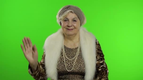 Ältere stilvolle Großmutter. Kaukasische Frau winkt mit den Händen, grüßt. Chroma-Schlüssel