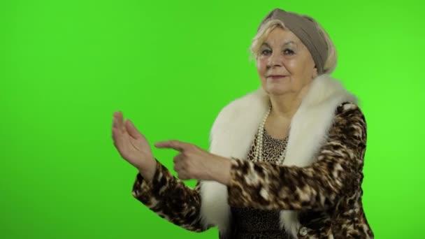 Ältere stilvolle Großmutter. Kaukasische Frau zeigt mit der Hand auf etwas
