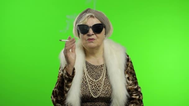 Ältere stilvolle trendige Großmutter. Kaukasische Frau raucht Zigarette. Chroma-Schlüssel