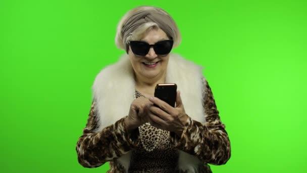 Ältere stilvolle trendige kaukasische Großmutter mit Smartphone. Chroma-Schlüssel