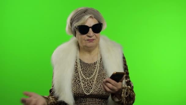 Ältere kaukasische Großmutter nutzt Smartphone zum Einkaufen. Chroma-Schlüssel