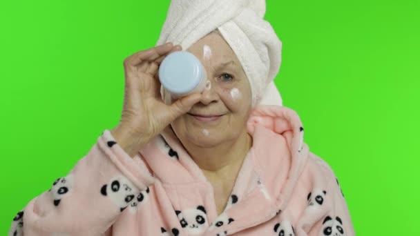 Ältere Großmutter im Bademantel. Alte Seniorin mit feuchtigkeitsspendendem Sahneglas