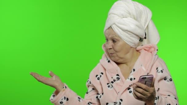 Ältere Großmutter im Bademantel. Alte Frau mit Smartphone zeigt auf etwas
