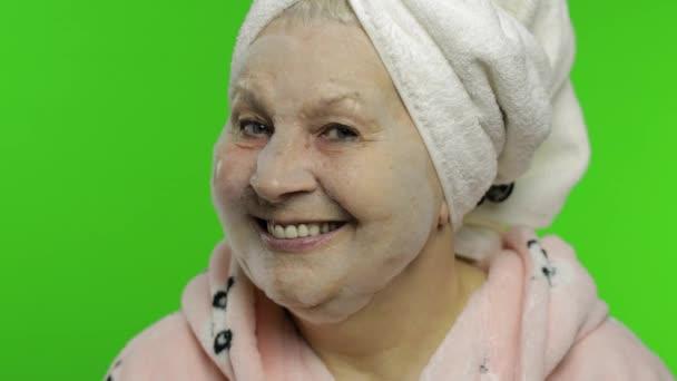 Ältere Großmutter nach der Dusche. Alte Frau Anwendung kosmetischer Blase Gesichtsmaske