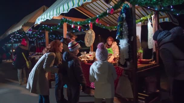 Children and their parents are looking at beautiful items at one of the stands on Christmas market.