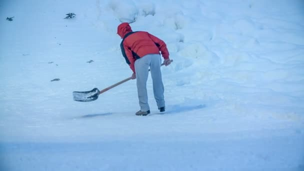 Ein Mann bereitet die Piste für den nächsten Skispringer vor. er hält eine Schaufel.