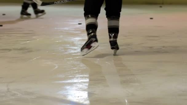 Existuje mnoho puky na ledě a hokejisté jsou plácání je do cílů na obou stranách kluziště.