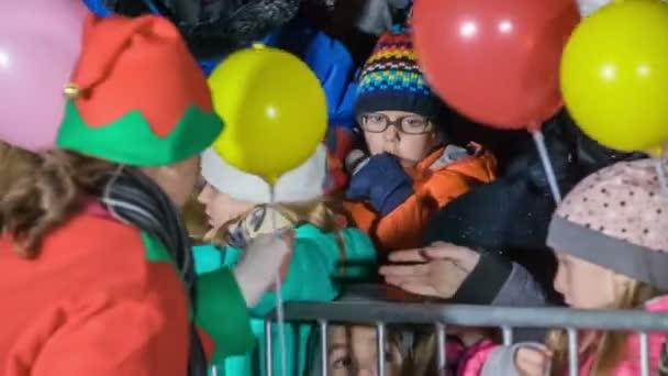 Weihnachtsmann-Helfer verteilen bunte Luftballons an die Kinder.