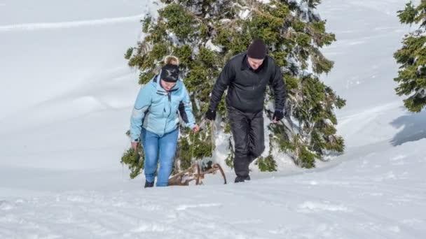 Ein Mann und eine Frau ziehen ihre Schlitten bergauf. Sie genießen es, den Berg hinunter zu rodeln und gemeinsam einen tollen Tag zu haben.