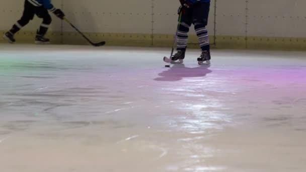 Hokejista hraje s pukem a on tlačí trochu doleva a doprava.