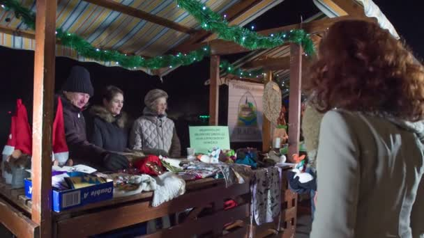 Visitors at Christmas market are looking at items at one of the Christmas stands.