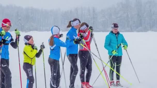 Junge Mädchen und Jungen stehen auf dem Schnee und warten in der Reihe. Es schneit. Sie werden bald mit dem Üben beginnen.