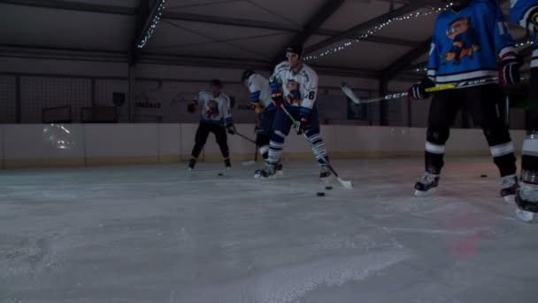 Hráči hokeje čekají ve frontě a začnou házet puky do branky jeden po druhém.