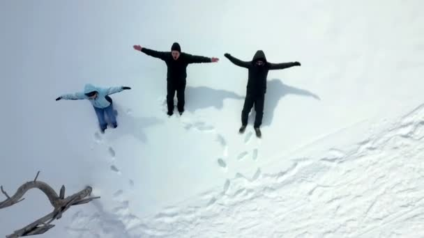 Three people throws themselves into the snow and make snow angels. Aerial shot.