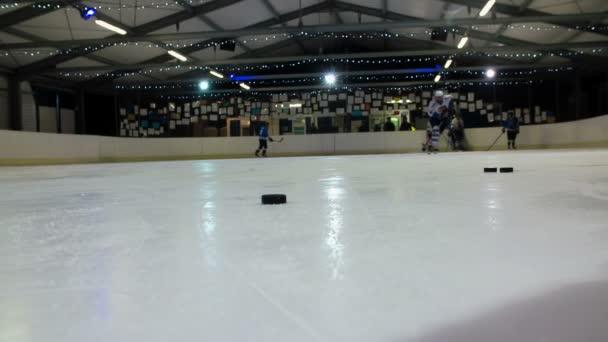 Na ledě na kluzišti je mnoho puků. Cvičí jen jeden hokejista a ostatní stojí na okraji kluziště..