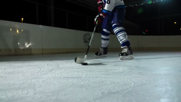 Hokejista si hraje s pukem na ledě. Pohybuje se doprava a pak doleva..