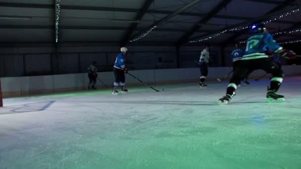 Hokejisté se zahřívají na kluzišti. Oni jsou plácání puky do cíle.