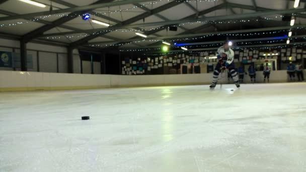 Hokejista je plácání puk do cíle a pak bruslení pryč.