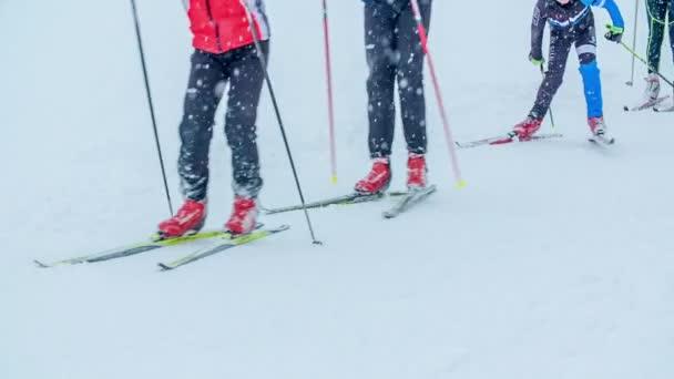 Die Skifahrer fahren dicht an dicht. Es schneit auch, aber sie haben eine richtig gute Zeit.