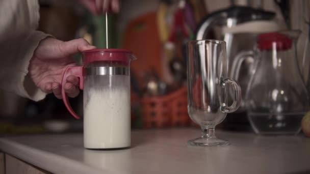 Člověk připravuje mléko na kávu