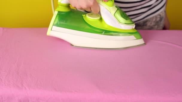 Dívka žehličky ložní prádlo na žehlícím prkně, domácí práce.