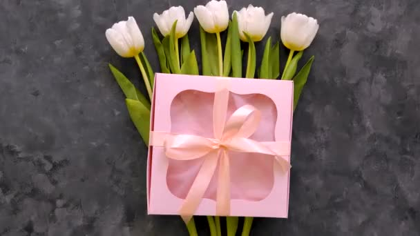 White tulip flowers with pink gift box on dark grey background flat lay. 4K video top view. 8 March Happy Womens Mothers Day concept. Spring flower bouquet,ribbon bows presents,female blog advertising