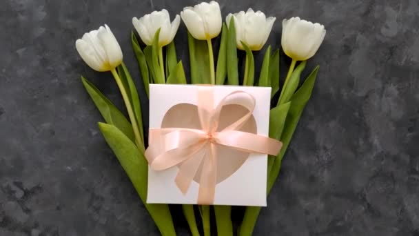 White tulip flowers, heart gift box with pink ribbon bow on dark grey background flat lay 4K video top view. Happy Birthday 8 March Women Mothers Day concept. Spring flower bouquet present,female blog