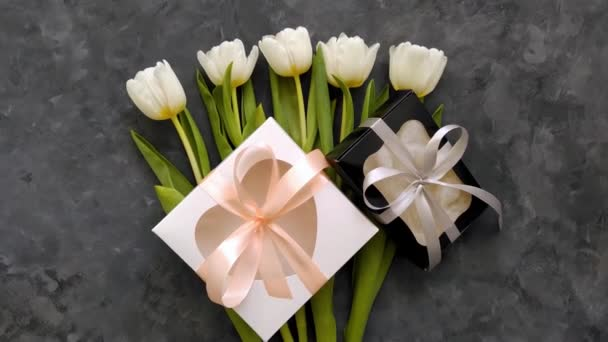 White tulip flowers, heart gift boxes with pink silver ribbon bows on dark background flat lay 4K video. Happy Birthday Holidays 8 March Women Mothers Day concept. Spring flower bouquet female blog