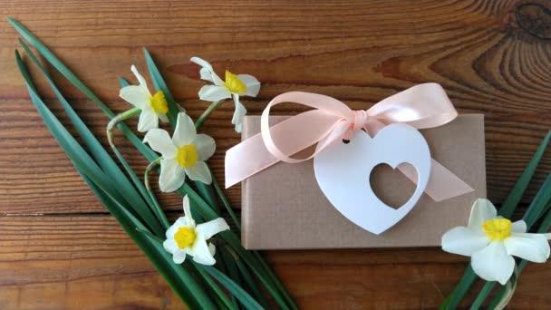 Bílé narcisy květiny a hnědé dárkové krabice na dřevěném pozadí 4K video. Dámská ruka dává srdce blahopřání s růžovou stuhou mašlí na současné balení. 8. března Happy Womens Matky Valentines Day