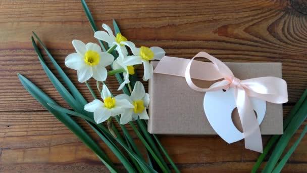 Bílé narcisy a hnědá dárková krabice, blahopřání s růžovou stuhou na dřevěném pozadí 4K video.Ženská ruka dává květiny kolem svátků dárkové balení. 8. března Happy Womens Matky Valentines Day