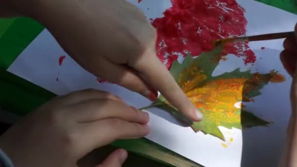 Children paint leaves with watercolors