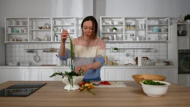 manželka v kuchyni připravuje jídlo a zachází se svým manželem