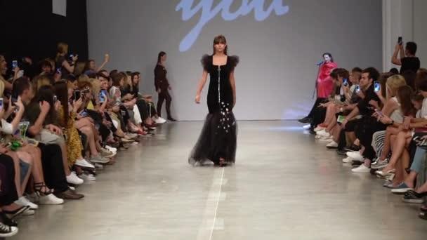 Dívka model na lávce na módní přehlídce