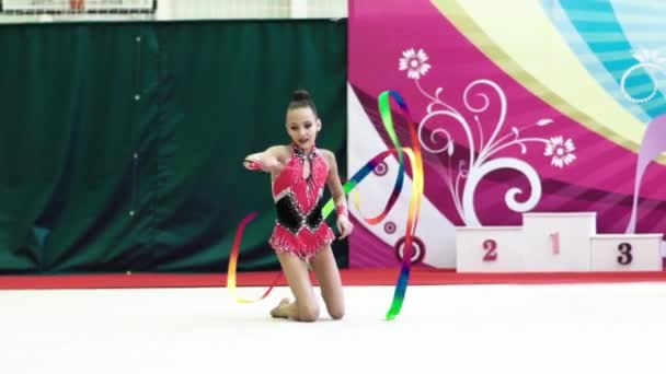 Girl gymnast with ribbon during the competition. Slow motion. Kyiv. Ukraine.
