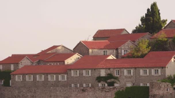 Domy s červenými kachlovými střechami. Architektura Sveti Stefana. Černá.