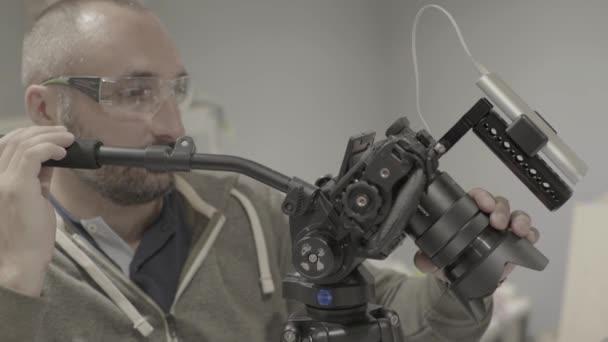 Primo piano di una fotocamera Dslr nelle mani di un fotografo cameraman durante le riprese di una foto video