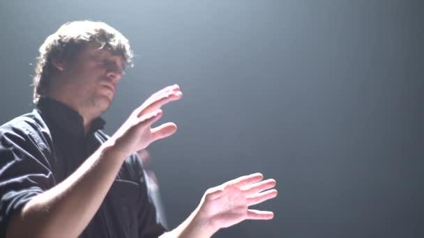 Ein männlicher Dirigent dirigiert auf der Bühne. Kiew. Ukraine
