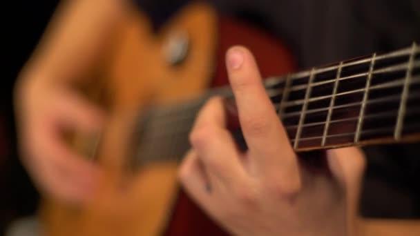 Muž kytarista hraje na kytaru ve tmě. Kyjev. Ukrajina