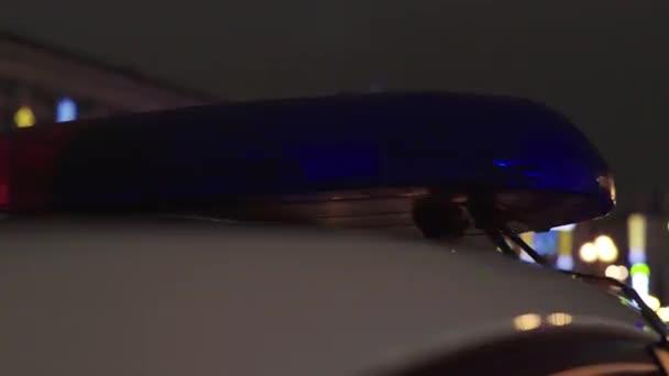 Blikající blikač na střeše policejního auta v noci. Blikač.