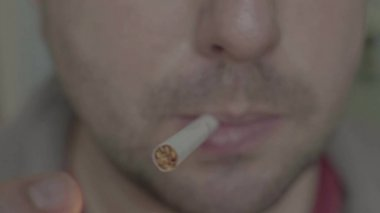 Cigarette in the mouth of a smoker. Close-up.