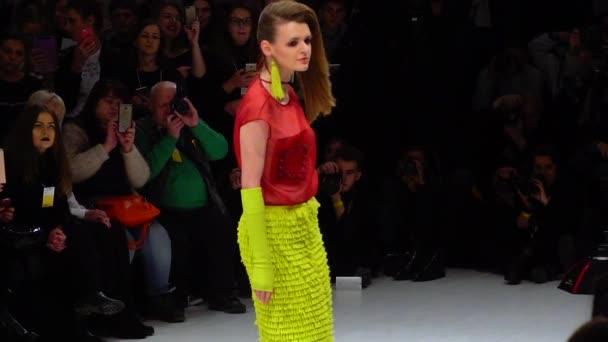 Fashion show. Girl model walking on the catwalk. Slow motion