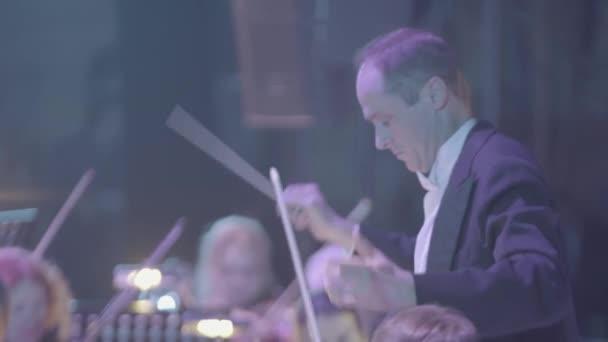 Mužský dirigent diriguje orchestr.
