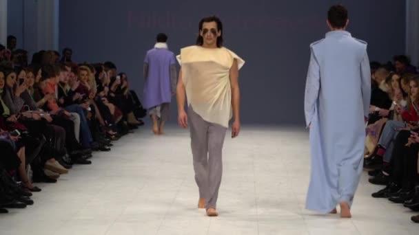 Módní přehlídka. Muž muž modelka chodí po lávce.