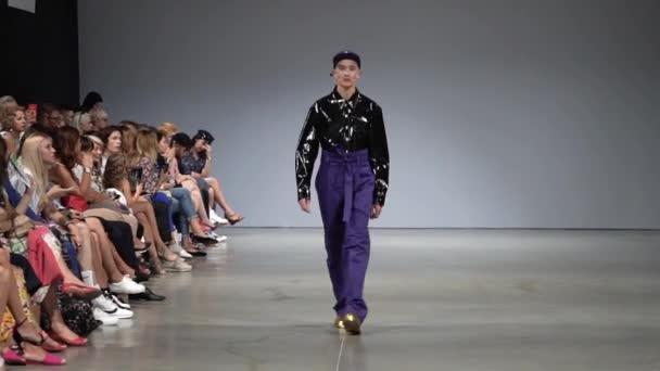 Divatbemutató. Férfi modell sétál a kifutón.