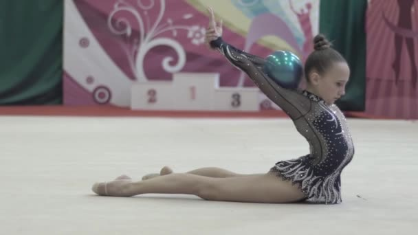 Girl gymnast with ball during the competition. Slow motion. Kyiv. Ukraine.