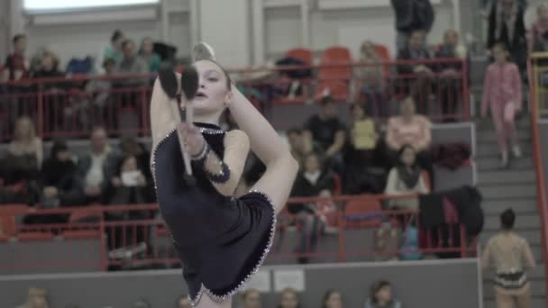 Girl gymnast with clubs during the competition. Slow motion. Kyiv. Ukraine.