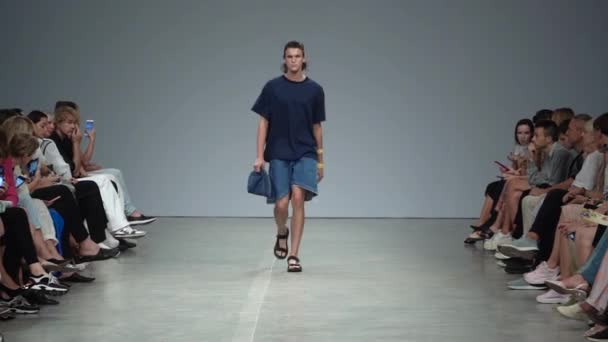 Fashion show. Male man model walks on the catwalk.