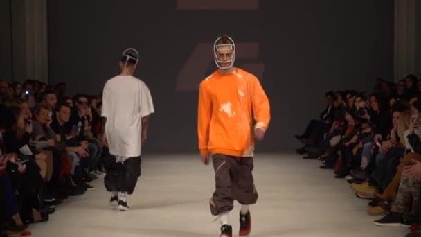 Fashion show. Male man model walks on the catwalk.