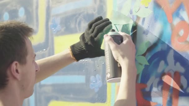 Drawing graffiti on a wall in the street